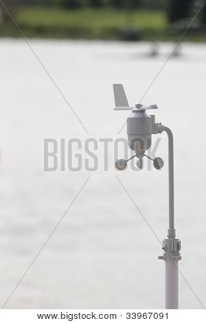 Anemometer and vane on a stand against a rowing stadium