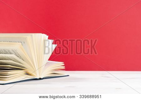 Composition With Vintage Old Hardback Book, Diary, Fanned Pages On Wooden Deck Table And Red Backgro