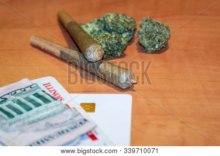 Recreational Cannabis Legalization In Illinois. Two Marijuana Joints Are Displayed With An Illinois