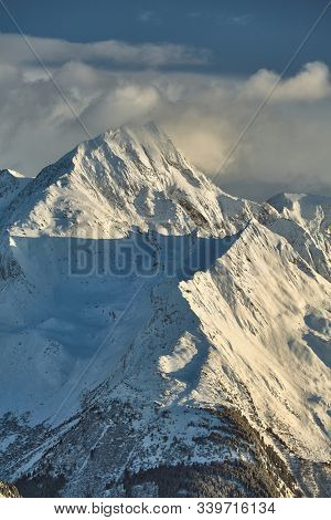 Snowy high mountains scenic landscape with clouds around the rocky peak