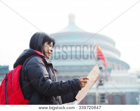 Asian Woman Looking At The Map Over Blur Background Of Great Hall Of Chongqing People's Square At Ch