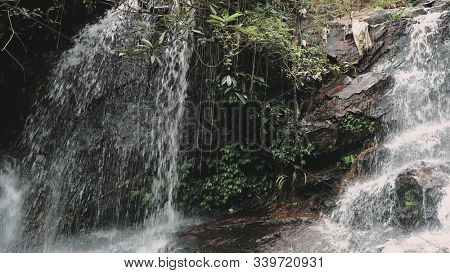 Mountain Cascade Waterfall Wild Spring Stream. Babbling on Rocks in Rainforest. Fresh Clear Water Running Down Fast. Tropical Forest Thailand Province.