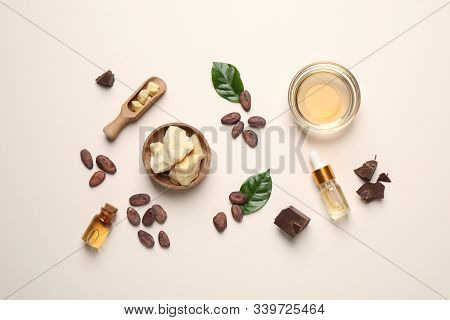 Organic Cocoa Butter, Beans And Essential Oil On Beige Background, Flat Lay