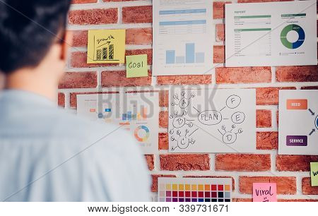 Asian Man Creative Director Designer Looking At Data Chart And Find Idea On Brickwall At Modern Offi