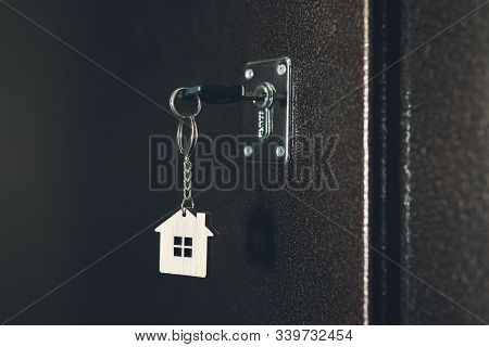 Process Of Opening The Front Door To The Apartment. House Model And Key In House Door. Real Estate A