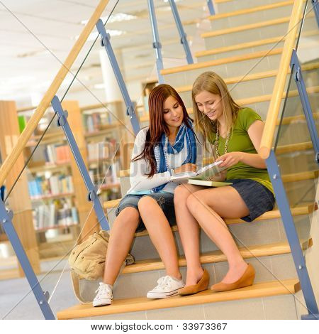 Brunette teenager with classmate studying on high school library stairs