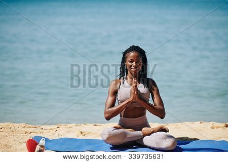 Happy Smiling Young Black Woman Sitting On Yoga Mat On The Beach And Keeping Hands In Namaste Gestur