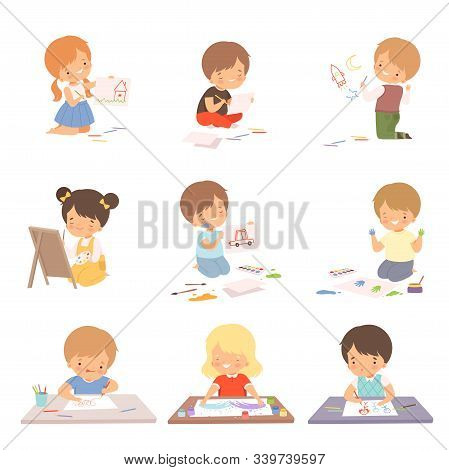 Cute Children Sitting On The Floor And Drawing Pictures With Colorful Pencils Set, Adorable Young Ar