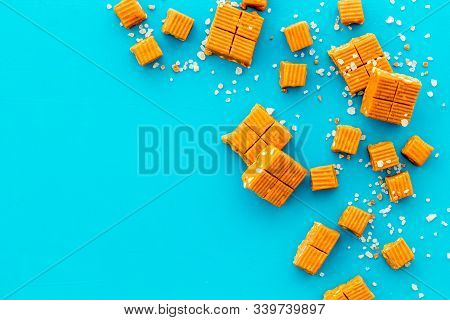Salted Caramel Pieces - Paradoxical Sweets - On Blue Background Top View Frame Copy Space