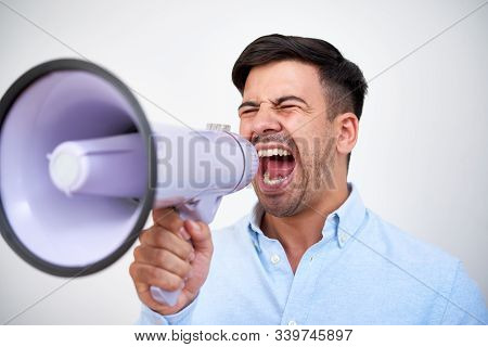 Young Man Closing Eyes When Screaming Out Loud In Megaphone At Business Meeting Or Political Gatheri