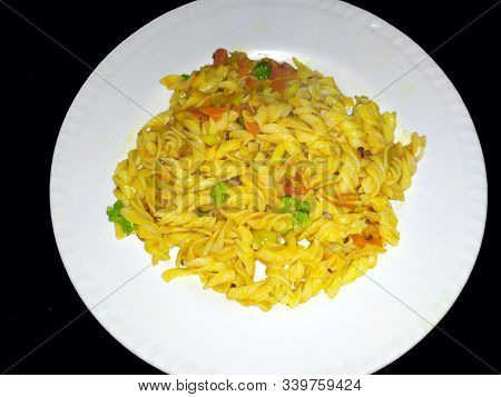 Some Yellow Eatable Food Put In A White Plate On Black  Background