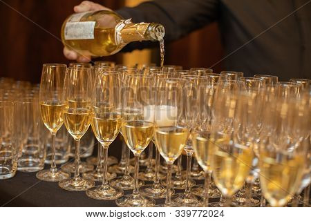Close-up Of A Sommelier Pouring Pinot And Champagne Into Glasses For A Tasting Celebration