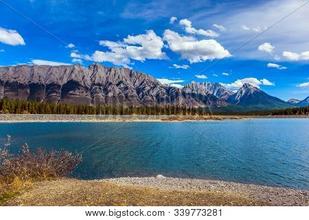 Autumn day in Indian summer. The Canadian Rockies. Magnificent mountain lake with emerald glacial water. Lakeshore overgrown with coniferous forests. The concept of ecological and photo tourism