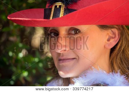 Happy showy young woman in a beautiful red wide-brimmed hat. Background - dense evergreen hedge. Concept - portrait and advertising photo
