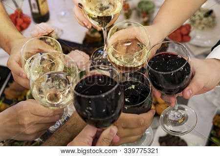 Friends Clinking Glasses Above Reataurant Dinner Table At Some Festive Occasion. People Drink Toasts