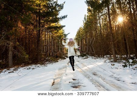 A Happy Energetic Woman Frolicks In The Snow Among The Forest Trees