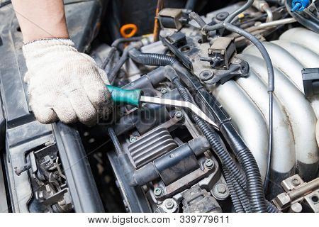 A Car Repairman Unscrews Parts With A Wrench With A Green Handle In The Engine Compartment Suh As Sp