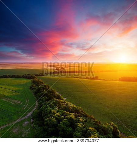 Aerial top view of green rural area under colorful sky at sundown. Location place of Ukraine, Europe. Drone photography. Perfect wallpaper. Concept of agrarian industry. Discover the beauty of world.