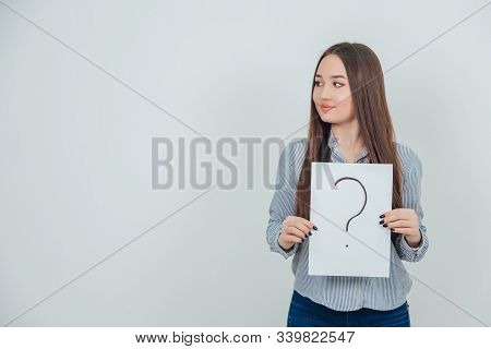 Inquisitive Asian Student Girl Holding A Sheet Of Paper With Question Mark Written On It, Looking To