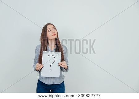Inquisitive Asian Student Girl Holding A Sheet Of Paper With Question Mark Written On It, Looking Up