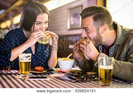 Happy Couple Having Fun Eating Burger At Restaurant Pub Fast Food - Young People Enjoying Moment At