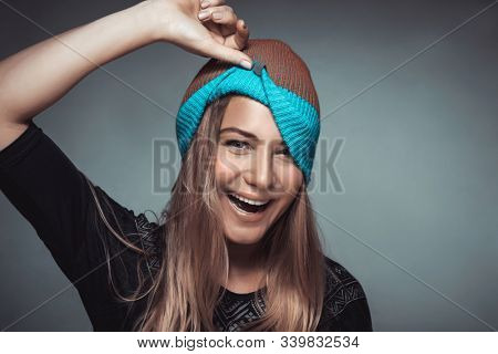 Portrait of a cute happy cheerful girl making faces and playing with a hat. Young model over gray background, funky urban style fashion for youngsters, joyful life