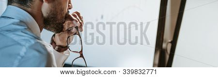 Panoramic Shot Of Bi-racial Trader Looking At Computer And Holding Glasses