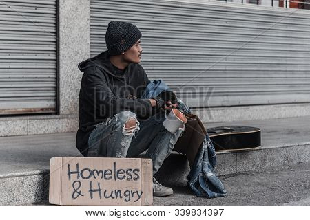 Dirty Hands Homeless Poor Man With Piece Of Bread In Modern Capitalism Society. Economic Recession,