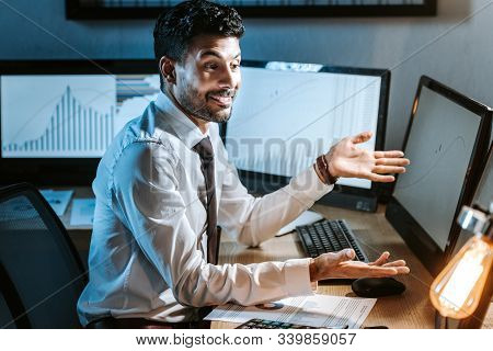 Smiling Bi-racial Trader Looking At Computer With Graphs In Office