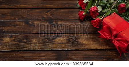 Bouquet Of Red Roses And Gift In Red Paper For Valentines Day