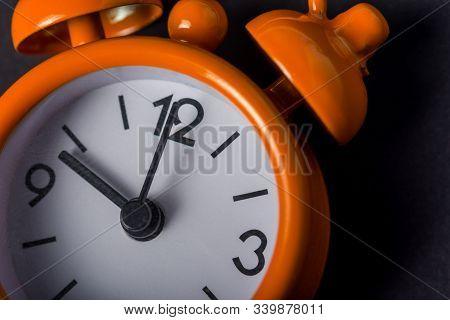 Bright Orange Clock On Black Background. Vintage Alarm Clock. Concept Of Time Management