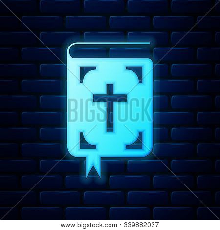 Glowing Neon Bible Book Icon Isolated On Brick Wall Background. Holy Bible Book Sign. Vector Illustr