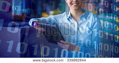 Binary code on blue circuit board against female factory worker standing with digital tablet in factory
