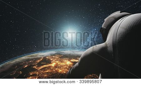 Cosmonaut looking at realistic planet Earth orbit. Sunrise over illuminated mainlands. Astronaut back view. 3d render animation. Science, technology concept. Elements of this media furnished by NASA.