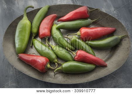 Mixed Red And Green Peppers On A Platter. A Close Up Studio Photo Of Red And Green Chili Peppers On