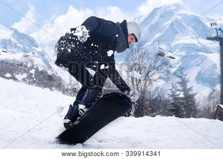 Snowboarder Is Jumping With Snowboard From Snowhill. Man Jumping Mountains Landscape In Background.s