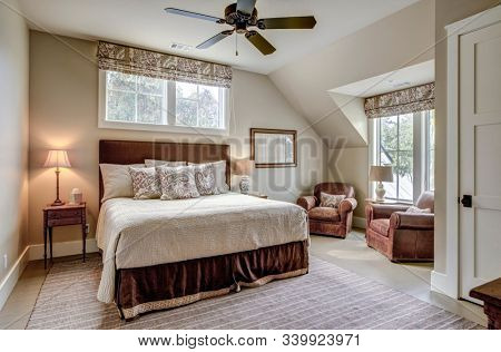Beautiful luxurious upstairs bedroom with ample windows and leather furniture.