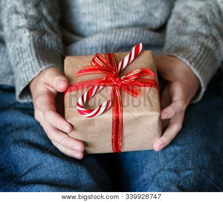 Female Hands Holding Gift Box With Red Ribbon And Striped Lollipop . Christmas, Hew Year, Birthday C