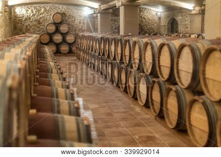 Row Of Old Oak Barrels Lie On Top Of Each Other In A Dry Cool Wine Cellar In Basement. Special Stora