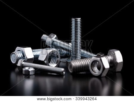 Bolts And Nuts Close Up. Industrial Still Life Of Metal Bolts And Nuts. Nuts And Bolts On A Black Ba