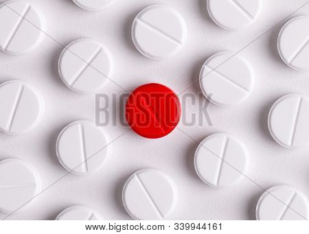 Background From Round White Medicinal Pills With A Single Red Pill In The Center. Special Medicine C