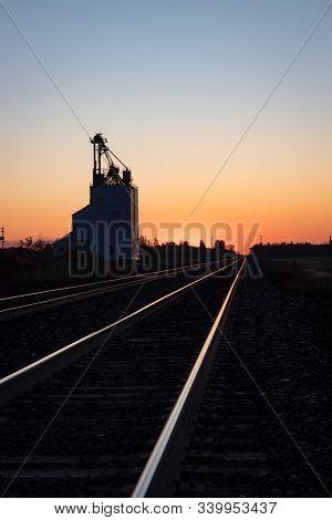 Vertical Crop Grain Elevator Silhouetted Against Golden Prairie Sunrise