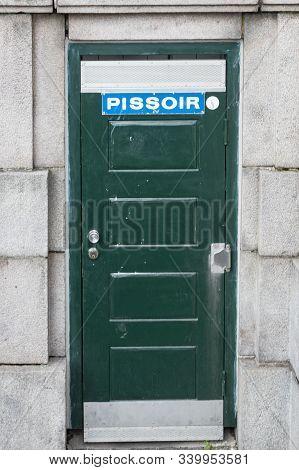 Blue Pissoir Sign On Green Door In Copenhagen