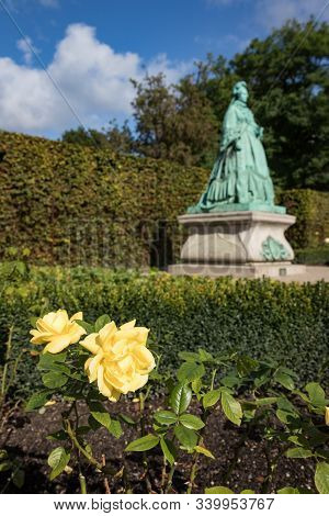 Yellow Flowers With Green Statue In Background