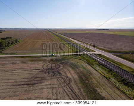 Aerial View Of Farm Fields And Double Train Tracks Across Prairie