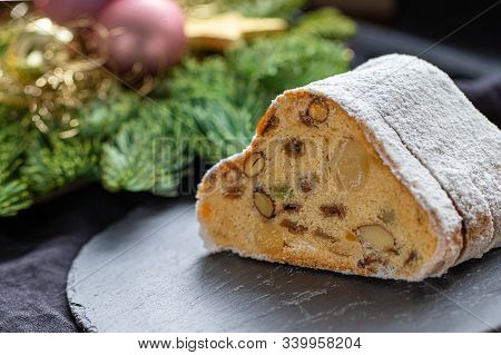 German Christmas Cake With Raisins And Nuts With Decoration In The Background