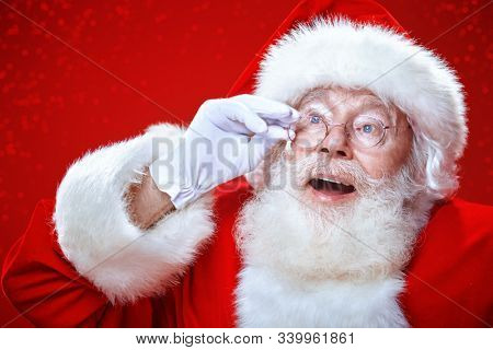 Close-up portrait of a jolly Santa Claus over festive red background. Merry Christmas and Happy New Year!