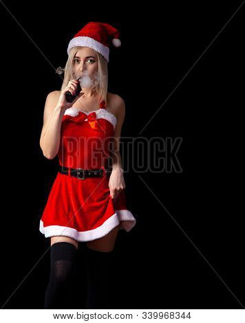 Young Beautiful Blonde Girl In A Sexy Red Snow Maiden Costume Or Santa Claus Is Smoking Vape And Exh