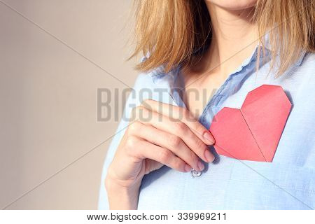Caucasian Woman Holding Origami Red Paper Heart, Puts Valentine In Breast Pocket. Insurance, Charity