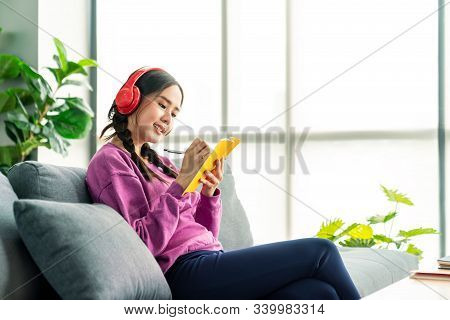 Candid Of Asian Woman Listening Podcast To Learning Online By Red Headphone. Asian Pretty Girl Enjoy